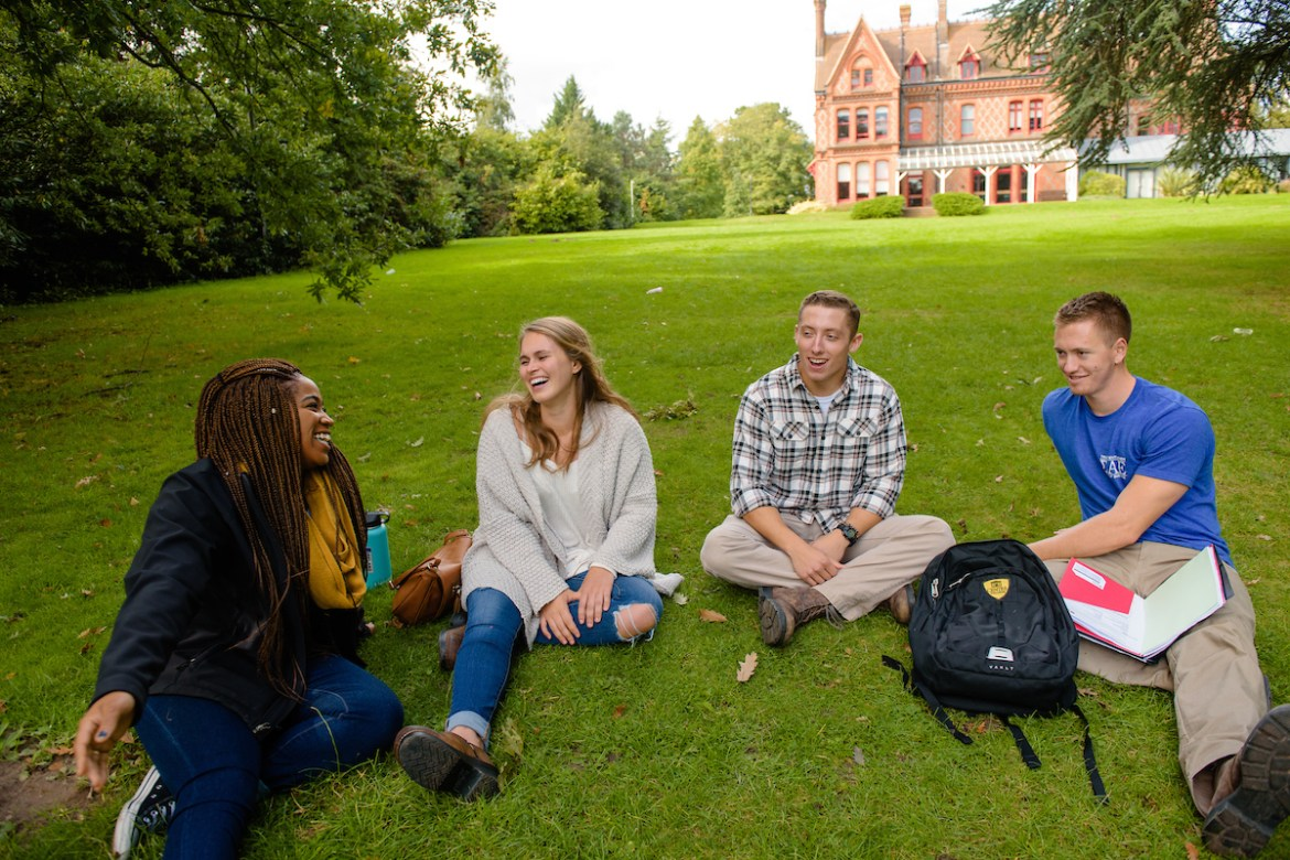 students sitting in the grass at the University of Reading in England