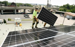 Eric Meyerhoffer '05 (Beard, Sunglasses) installs solar panels on the roof of Cowan on July 19, 2017. The solar panels are part of a student-led green initiative.