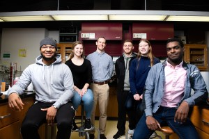 Daniel Scott posses for a portrait in a science lab with student research assistants.