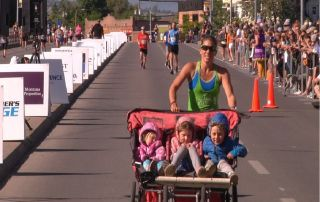 Lauren Arnold '06 running the Missoula Marathon while pushing her children in a triple stroller