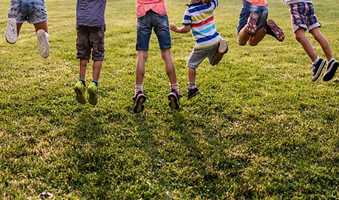 Bambini che saltano su un prato