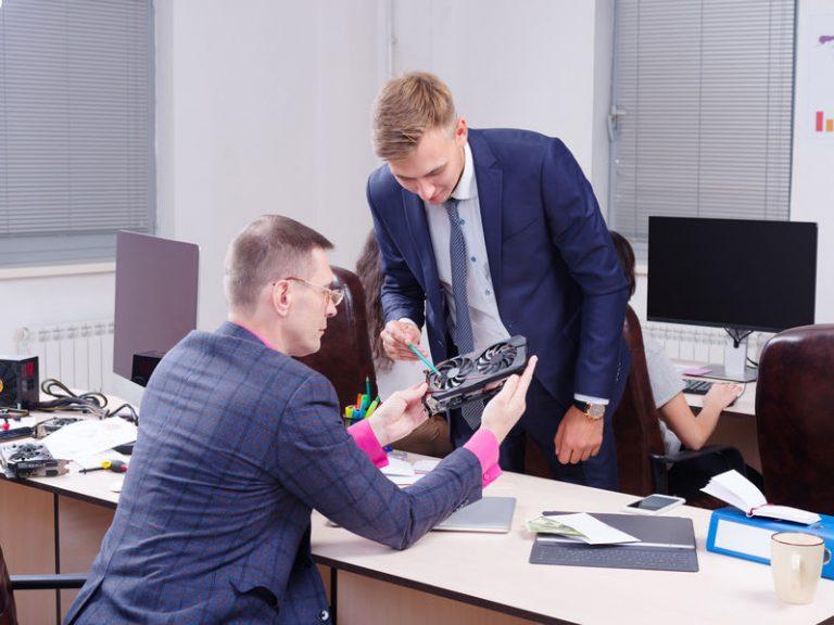Uomo che mostra una scheda grafica a un collega