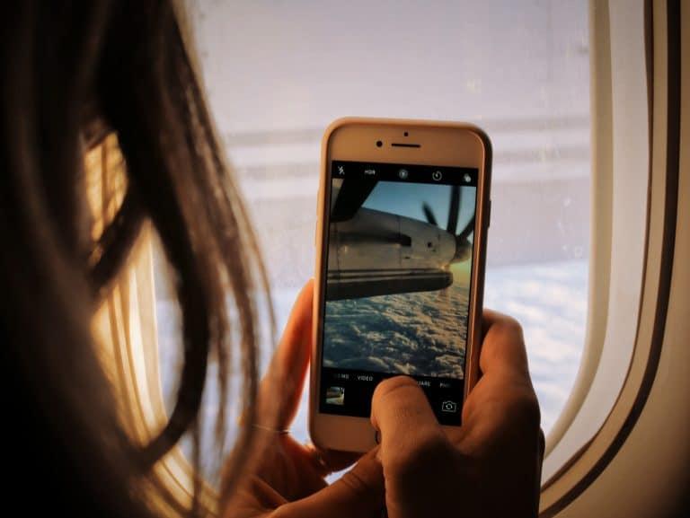 Ragazza che fotografa l'aereo con telefono