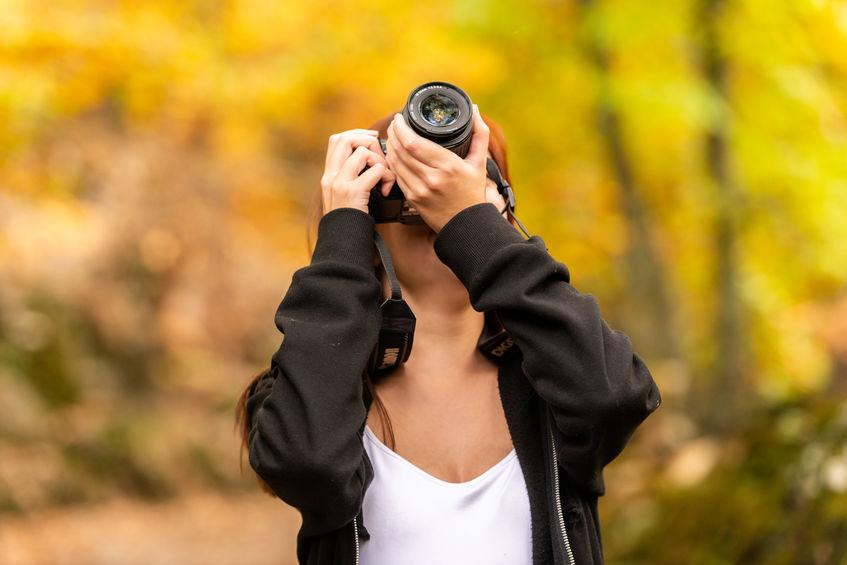 Una giovane donna dai capelli rossastri scatta foto con una reflex in una foresta