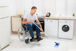 Disabled Man On Wheelchair Cleaning Floor With Mop In Kitchen Room
