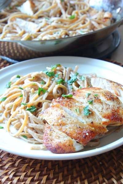 chicken cut up on a plate with pasta and a pan of chicken and pasta