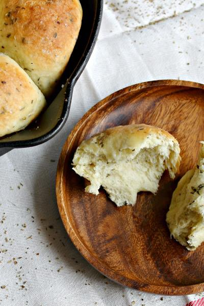 garlic herb rolls in a cast iron pan with a roll on a plate