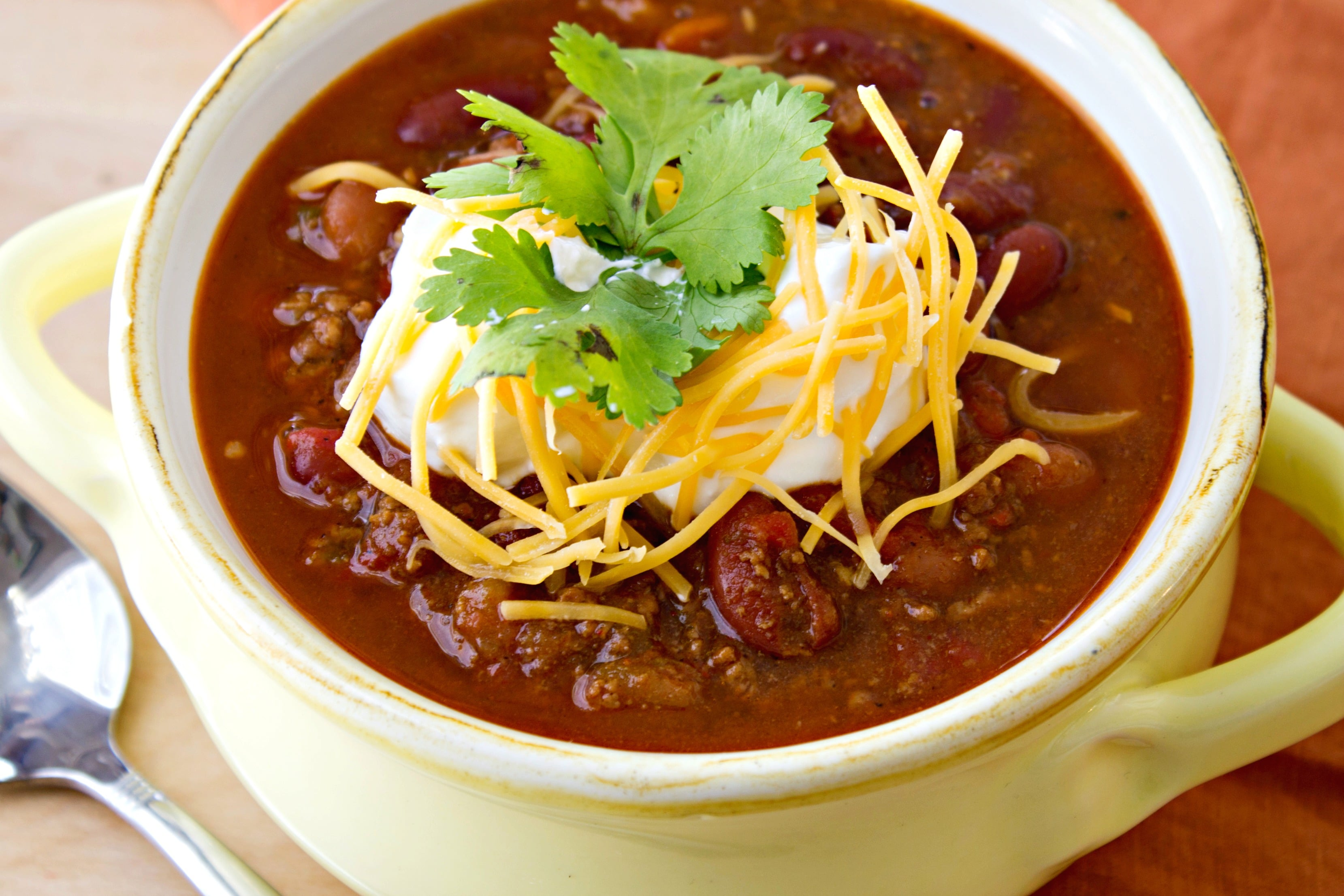 Cup Of Chili With Cheese, Sour Cream And Cilantro On Top