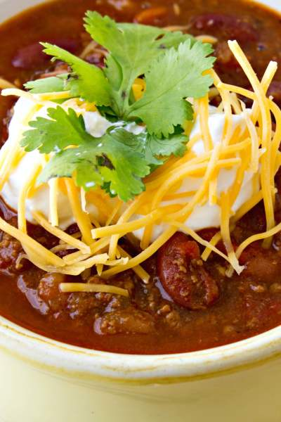 bowl of simple classic chili topped with sour cream cheese parsley and a spoon next to it, shot from a side angle