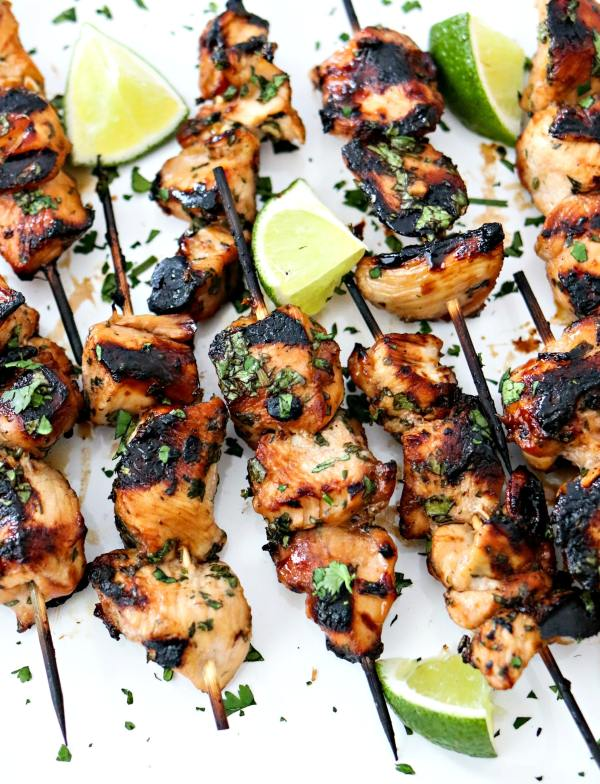 Grilled Cilantro Lime Chicken Skewers - This is the most tender and most flavorful chicken you will ever make! The chicken gets marinated in a honey, lime, cilantro, garlic, and soy sauce marinade for a few hours, skewered, and then grilled. Super easy and always a hit! Perfect for serving a crowd.