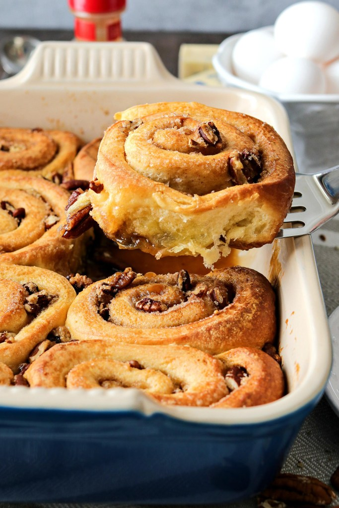a Pecan Sticky Buns on a spatula with a dish of more rolls