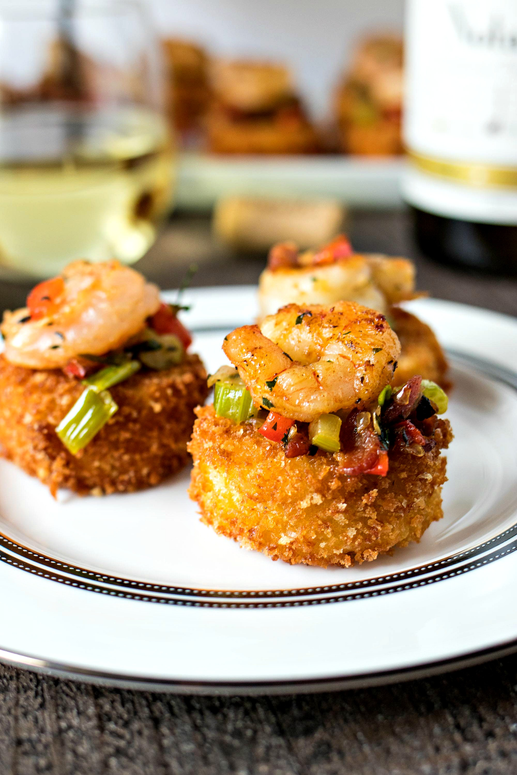 Shrimp & Cheesy Grit Cake Bites - Ultra creamy grit patties are fried and served with a buttery sauteed shrimp and crispy bacon to create an appetizer that your guests will go crazy for. Pairs perfectly with the flavors of Chardonnay wine!