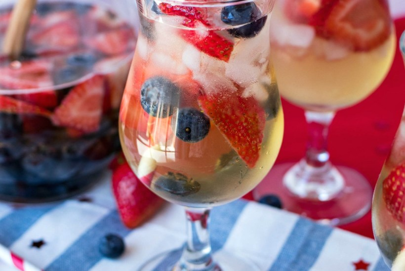 styled shot of Red, White, & Blue Sangria in glasses and a pitcher with blueberries and strawberries scattered around on cloth napkins