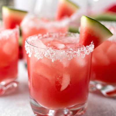 styled shot of glasses of Watermelon Margaritas with ice cubes and slices of watermelon and the rim with salt on it