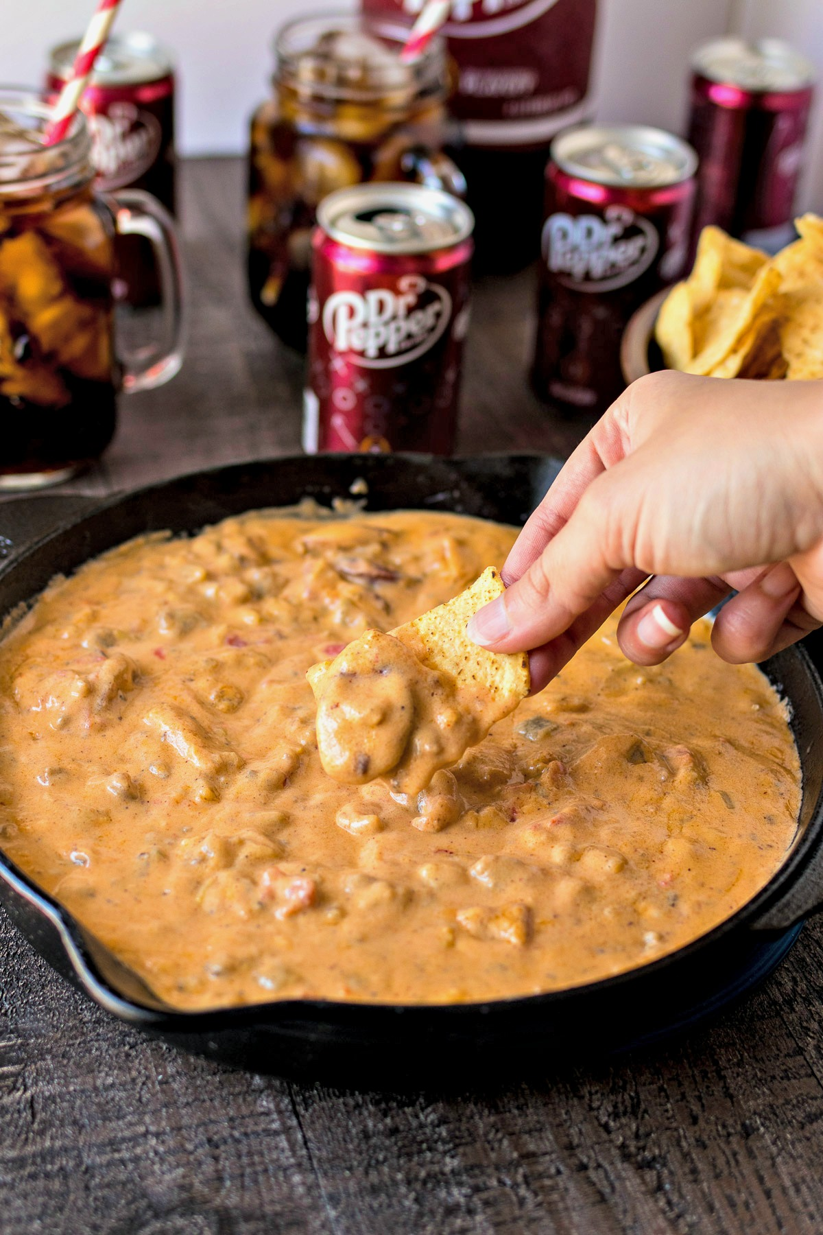 Dipping a tortilla chip into a skillet of Cowboy Queso