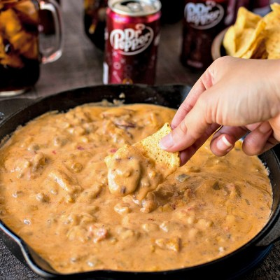 Cowboy Queso - A chunky queso dip with chopped green chiles, roasted tomatoes, ground sausage, and sliced smoked cheddar sausage. The best dip to feed a hungry crowd during a tailgate. Perfectly pairs with ice-cold Dr Pepper!