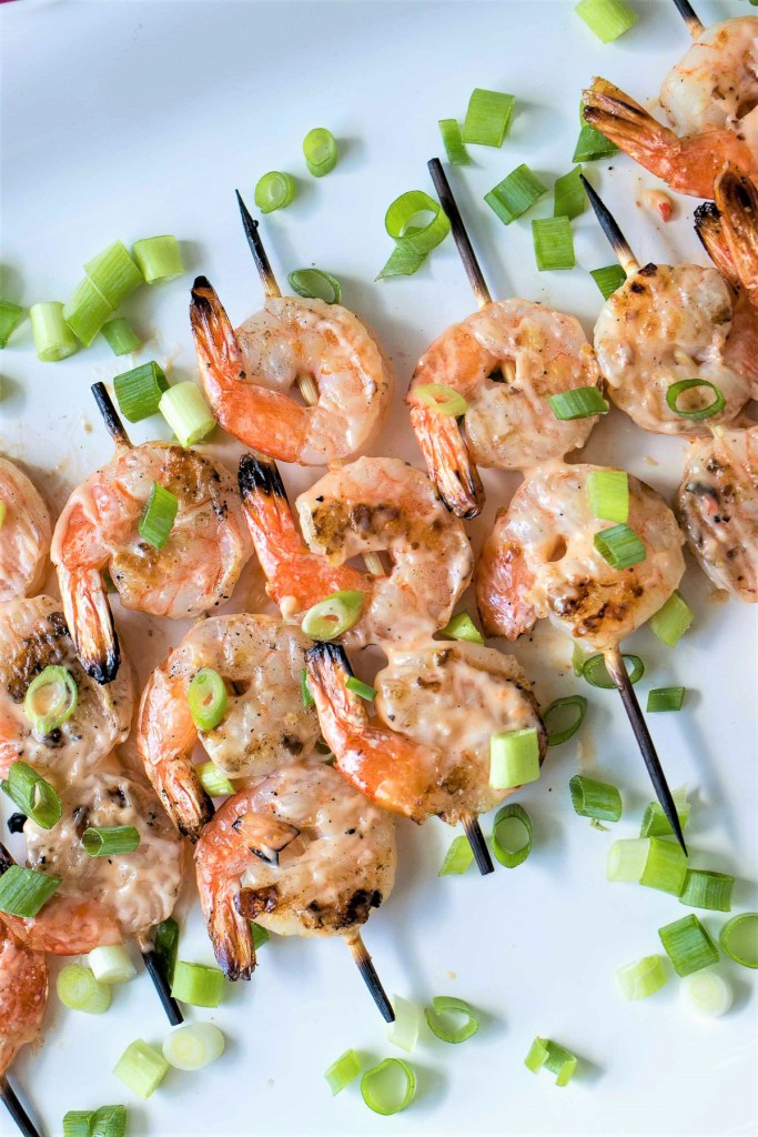 Grilled Bang Bang Shrimp Skewers with scallions sprinkled around them, shot from overhead