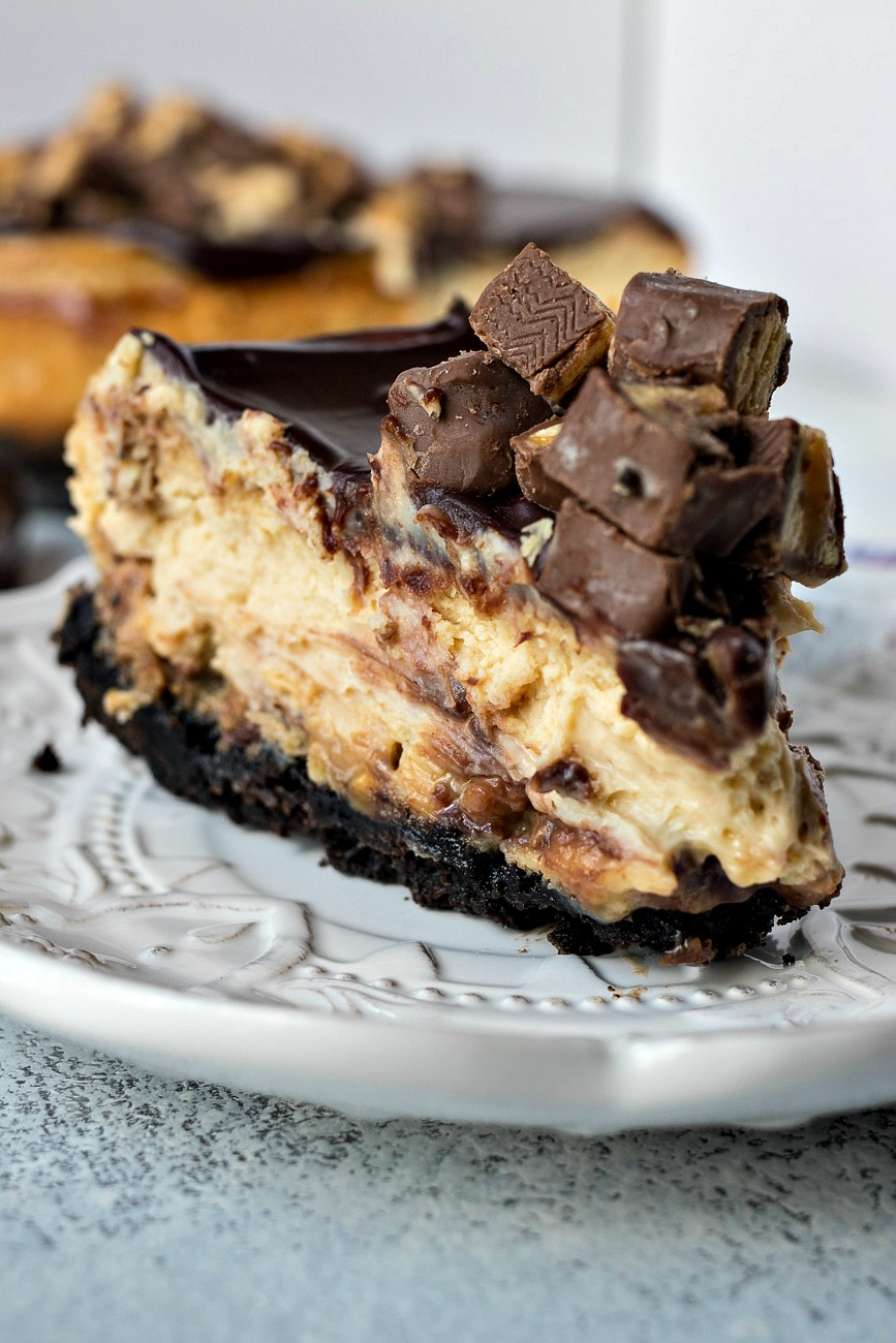 Slice of Snickers Cheesecake topped with snickers pieces