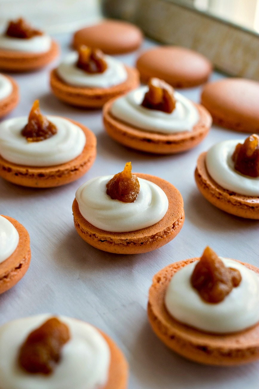 Pumpkin Cheesecake Macaron bottoms with cream cheese filling and a drop of pumpkin