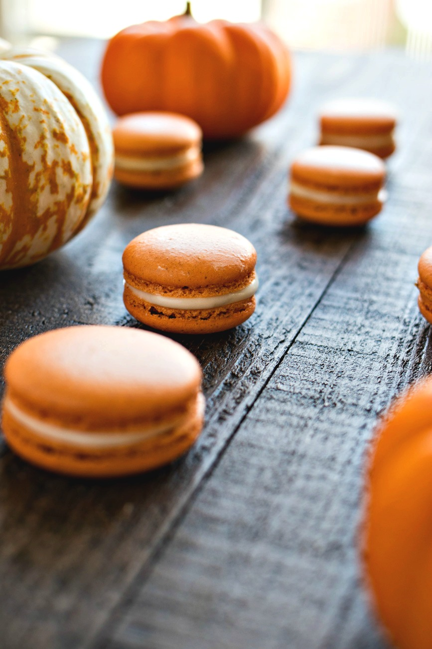 Pumpkin Cheesecake Macarons in front of a pumpkin