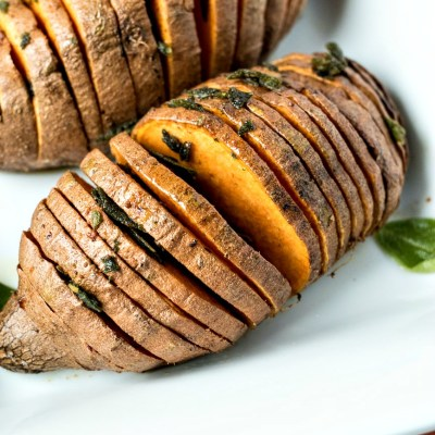 zoomed in shot of Sage & Browned Butter Hasselback Sweet Potatoes, shot from a side angle