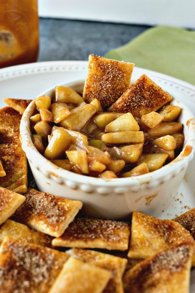 a bowl of Salted Caramel Apple Pie Dip in a bowl with two Pie Crust Chips in it and more pie crust chips next to them on a plate and a jar of salted caramel in the background, shot from a side angle