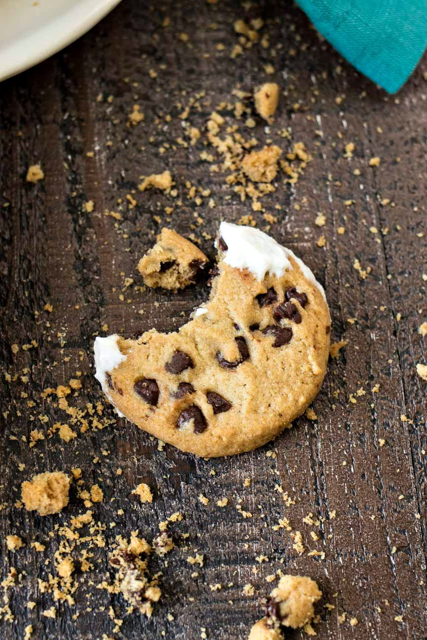Chocolate chip cookie with a bite out of it after being dipped in Classic Cannoli Dip