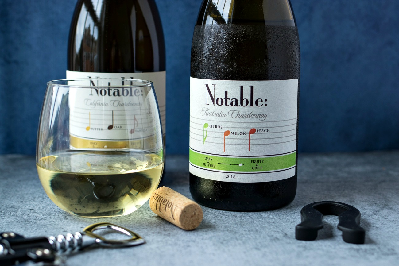 Glass of white wine in front of two bottles of Notable brand chardonnay