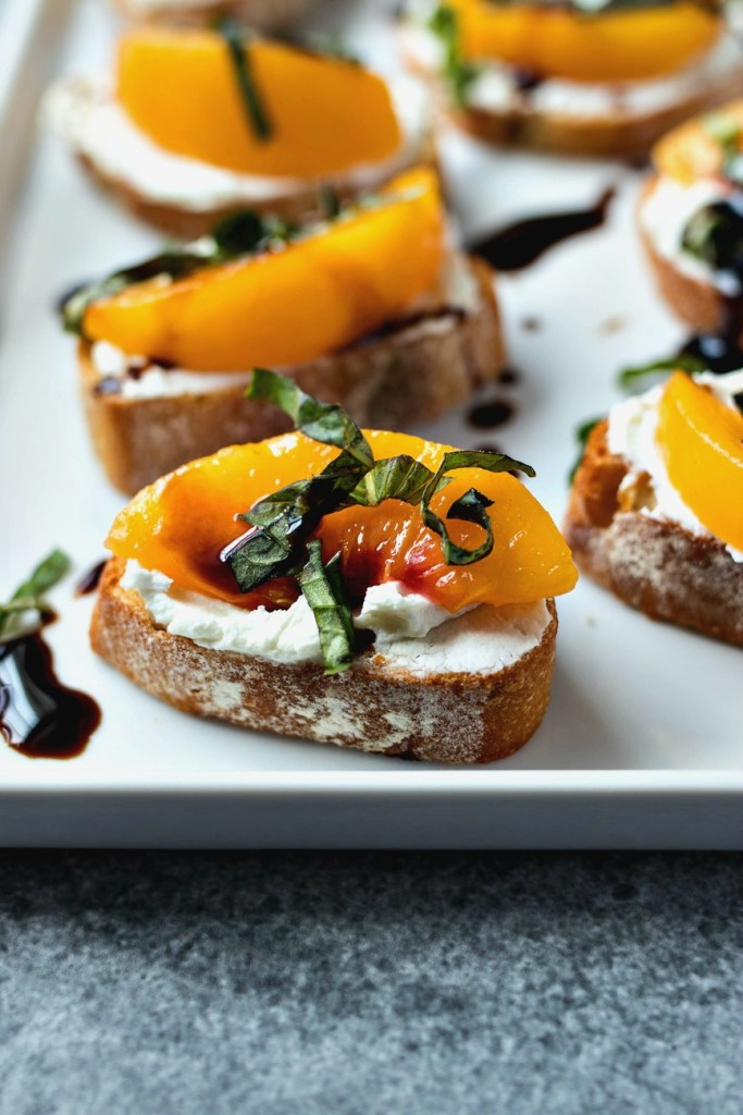 Peach & Goat Cheese Crostini on a platter topped with basil and balsamic glaze, shot from overhead