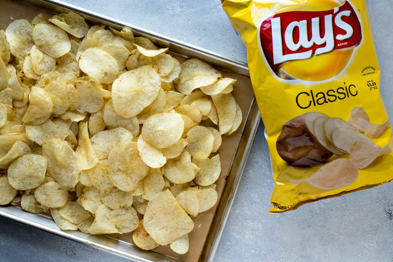 Sheet of Lays classic chips next to a bag of Lays chips
