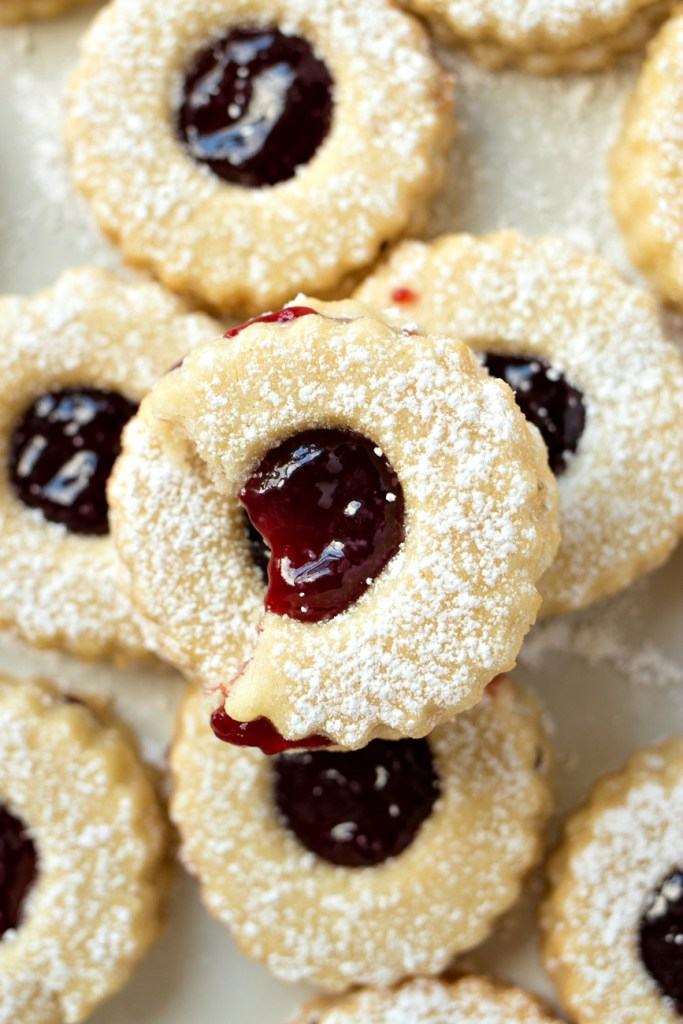 a plate of Raspberry Almond Linzer Cookies, shot from overheadrt raspberry jam sandwiched between two buttery almond shortbread cookies