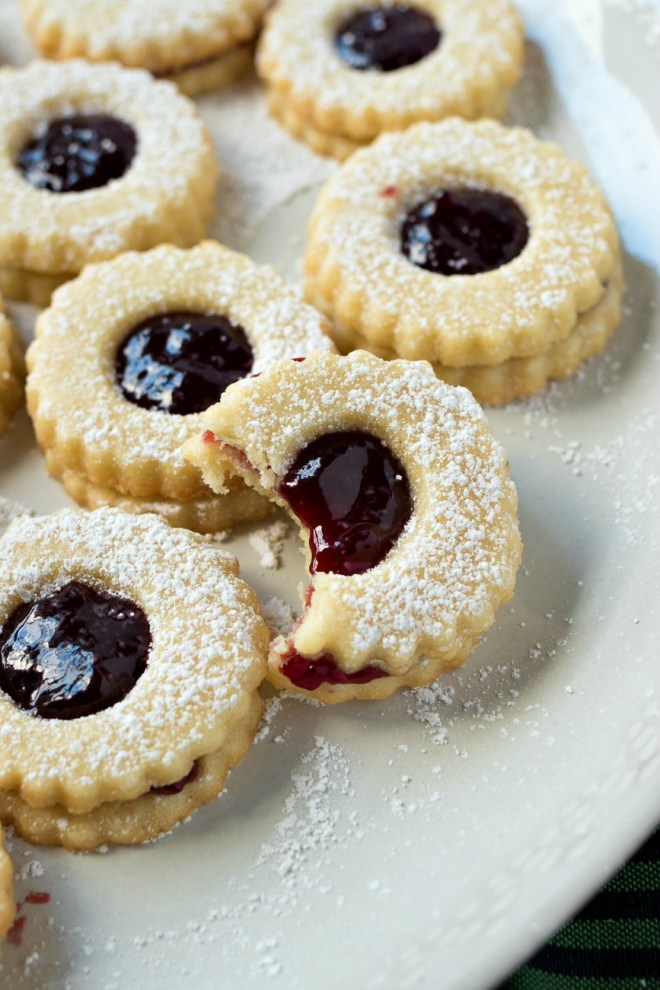 Raspberry Almond Linzer Cookies - Perfectly tart raspberry jam sandwiched between two buttery almond shortbread cookies