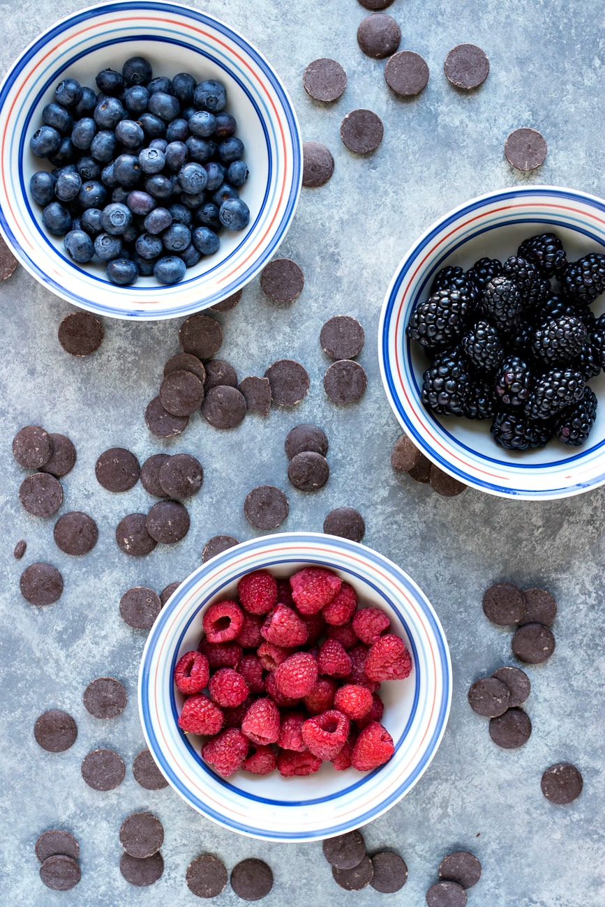 Bowls of blueberries, blackberries and raspberries surrounded by chocolate chips