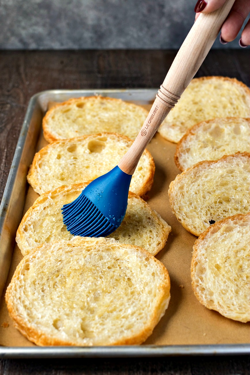 Brushing croissant pieces with melted butter
