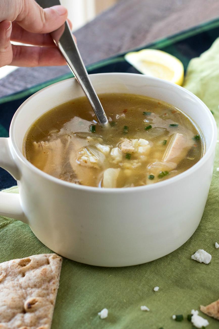 Bowl of Greek Lemon Chicken Soup with a spoon in it