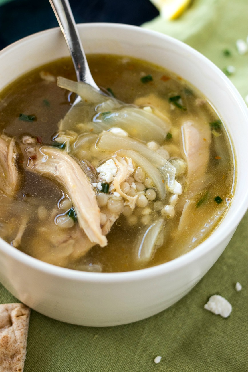 Spoonful of chicken, couscous and onions in a bowl of Greek Lemon Chicken Soup