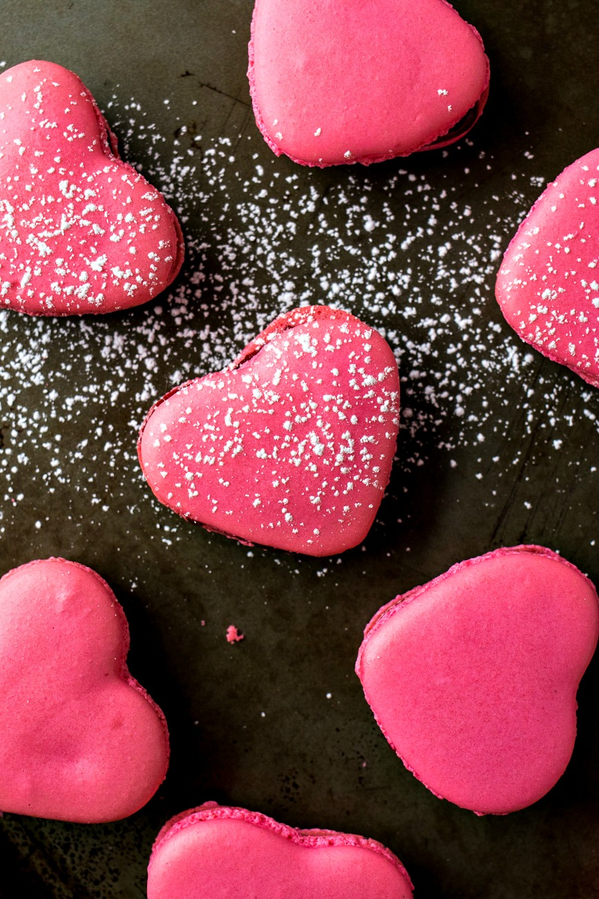 Raspberry Macaron Hearts - Classic french raspberry macarons are given a Valentine's Day makeover by shaping them into lovely hearts. Perfect to share with the one you love!