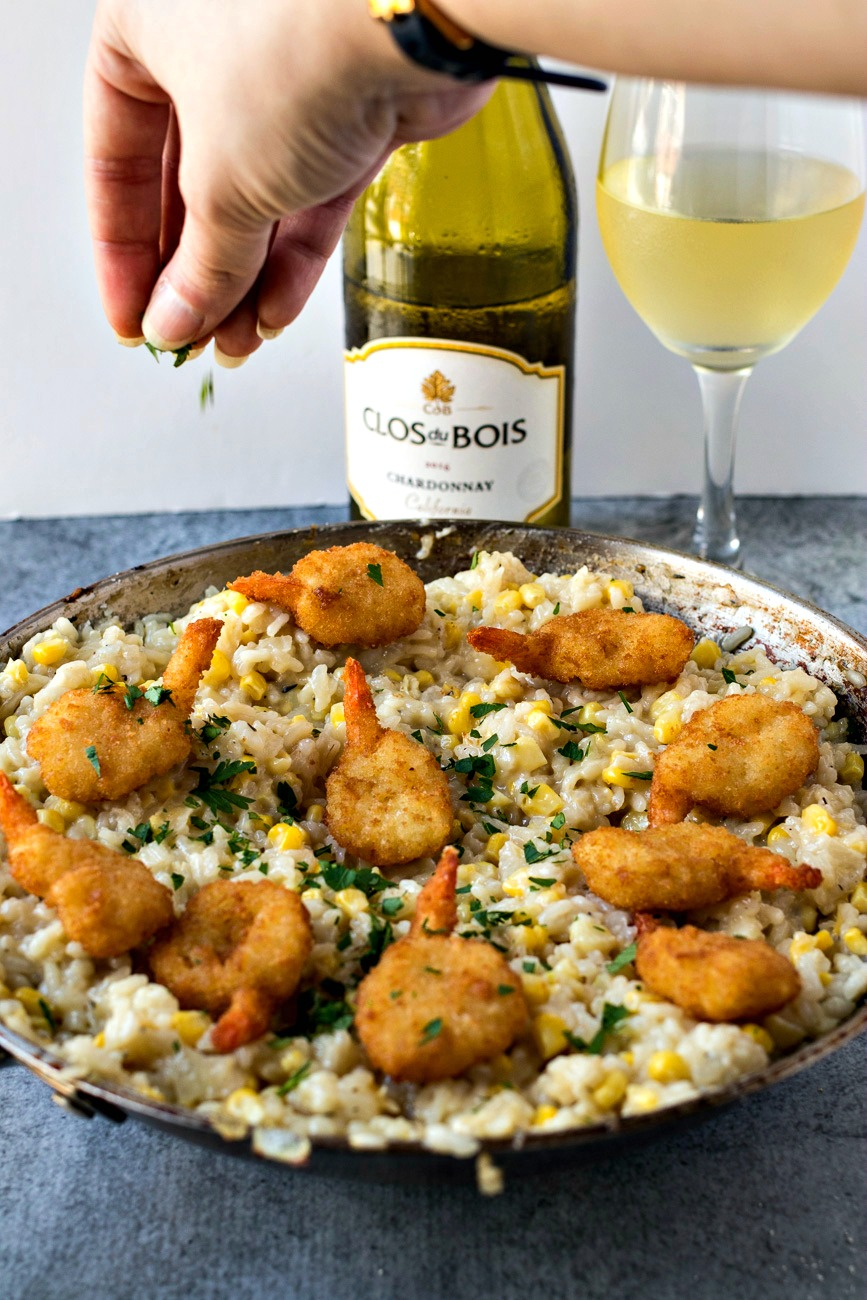 sprinkling garnish on top of the Sweet Corn Risotto with Crispy Shrimp