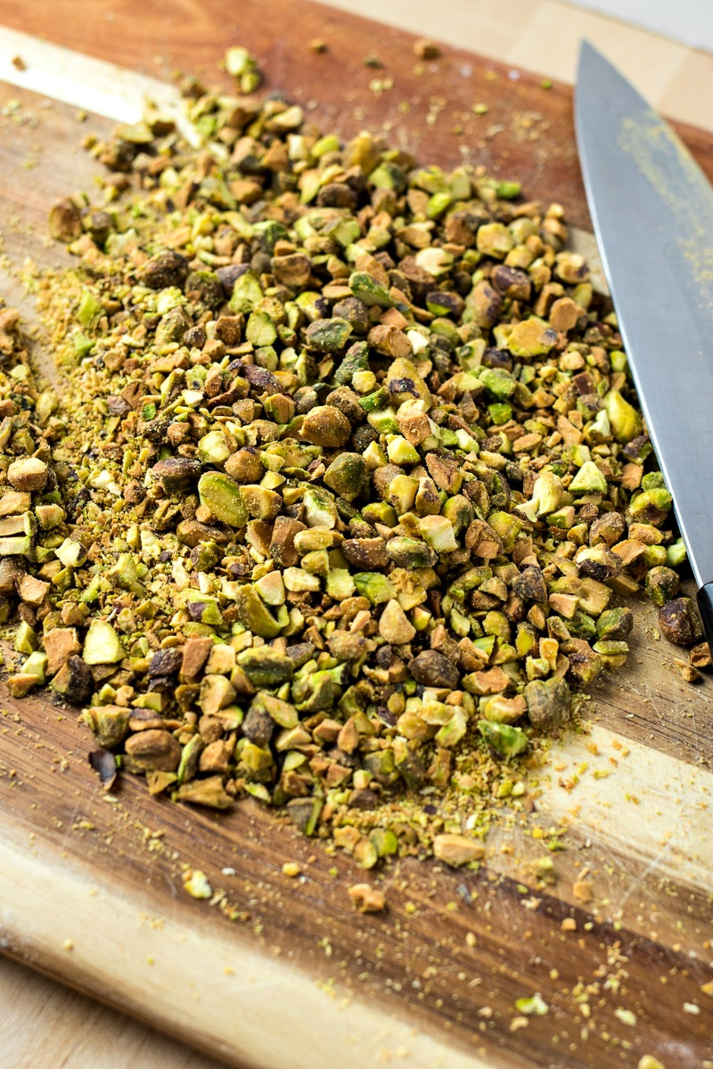 Cut up pieces of pistachio on a cutting board
