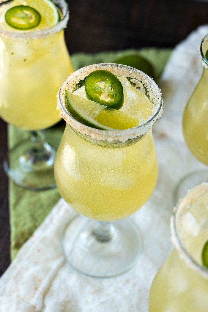 Glass of Sparkling Jalapeño Limeade with a lime wedge an jalapeno slice on top