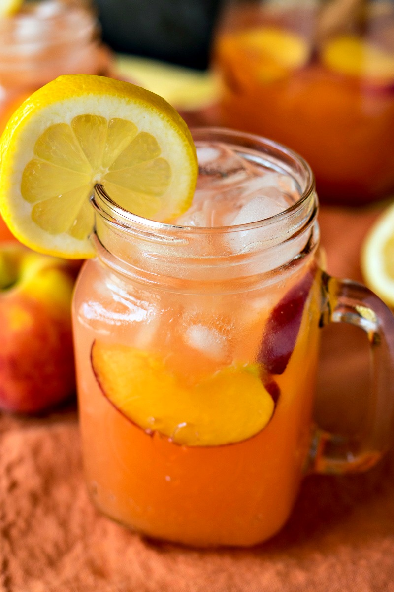 Glass of Peach Lemonade with peach slices and a lemon slice