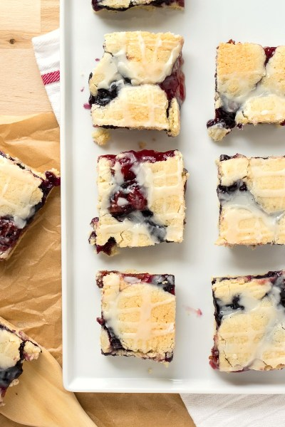 Red, White, and Blue Pie Bars - Cherry and blueberry pie filling are loaded into a soft, cakey bar that is finished with a gorgeous white glaze.