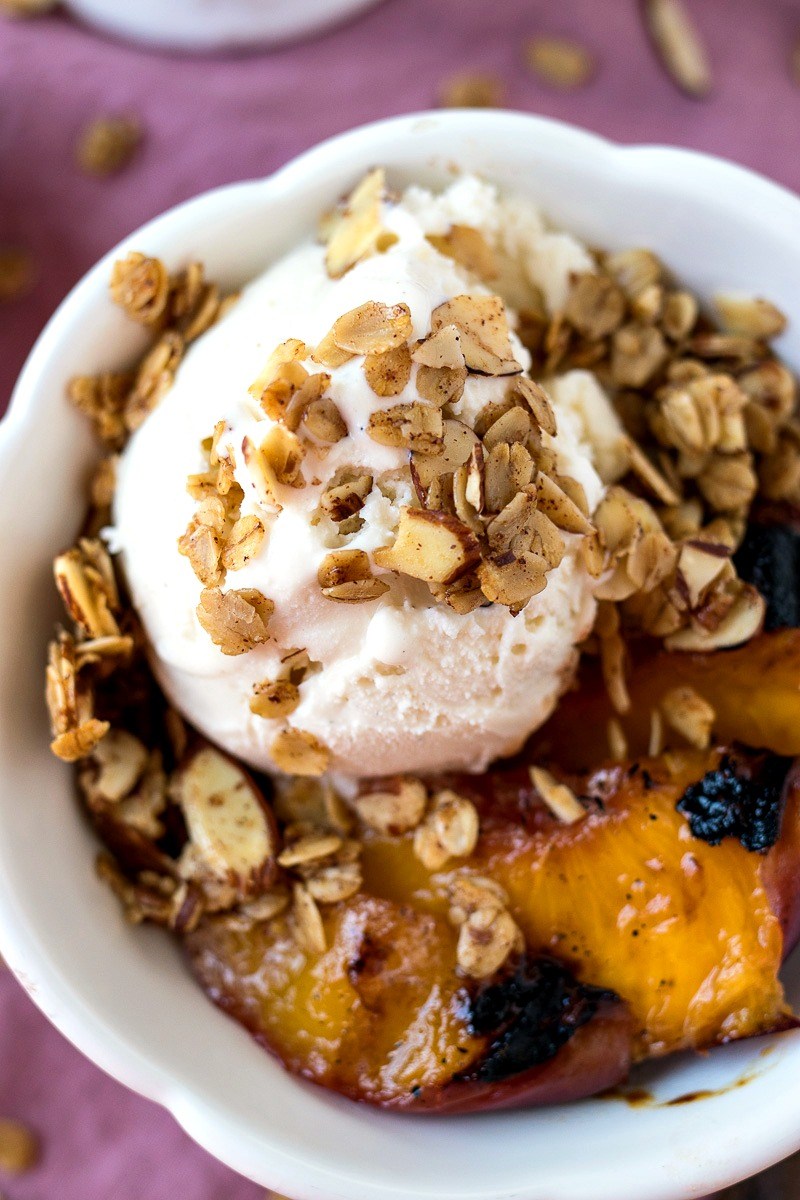 Closeup view of the vanilla ice cream and cinnamon granola on a Grilled Peach Sundae
