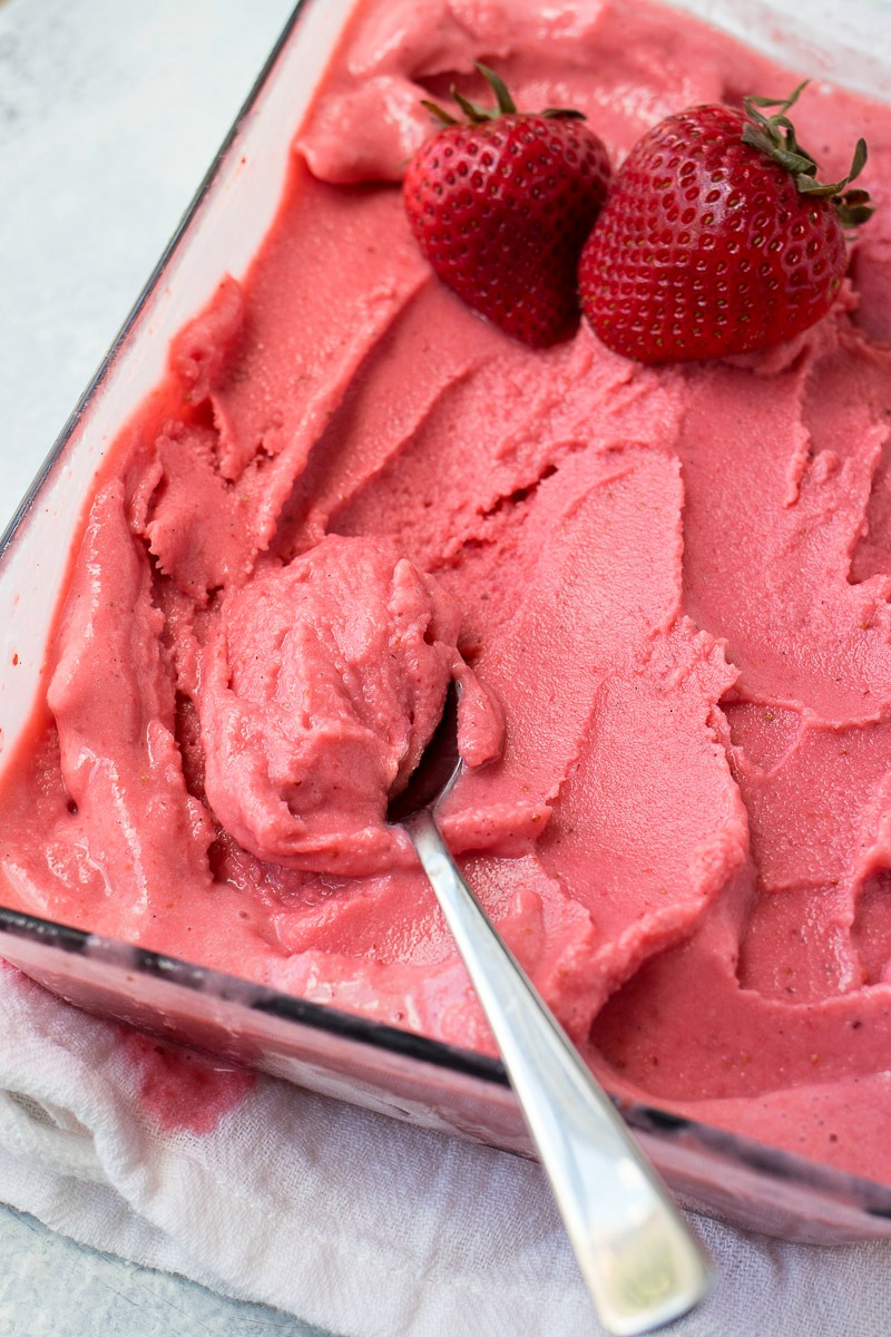 Pan of Strawberry Coconut Sorbet with a spoon scooping it out