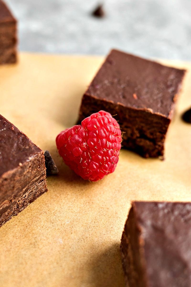 Closeup of a raspberry in front of a Dark Chocolate Raspberry Fudge square