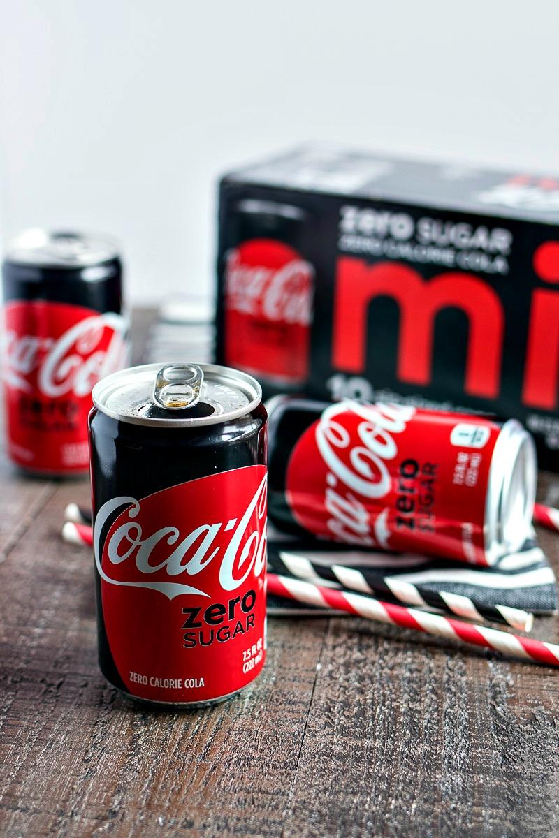 mini can of coke zero in front of a case of coke zero