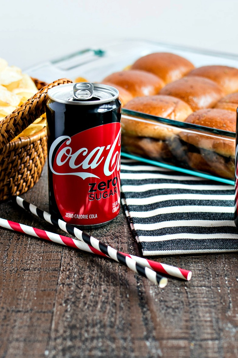 mini can of coke zero in front of a pan of Philly Cheesesteak Sliders