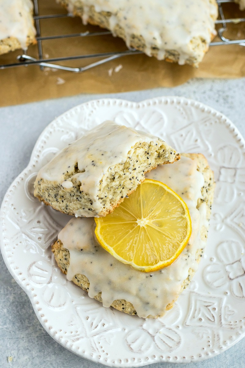 Lemon Poppyseed Scone cut in half on top of another iced Lemon Poppyseed Scone topped with a lemon slice