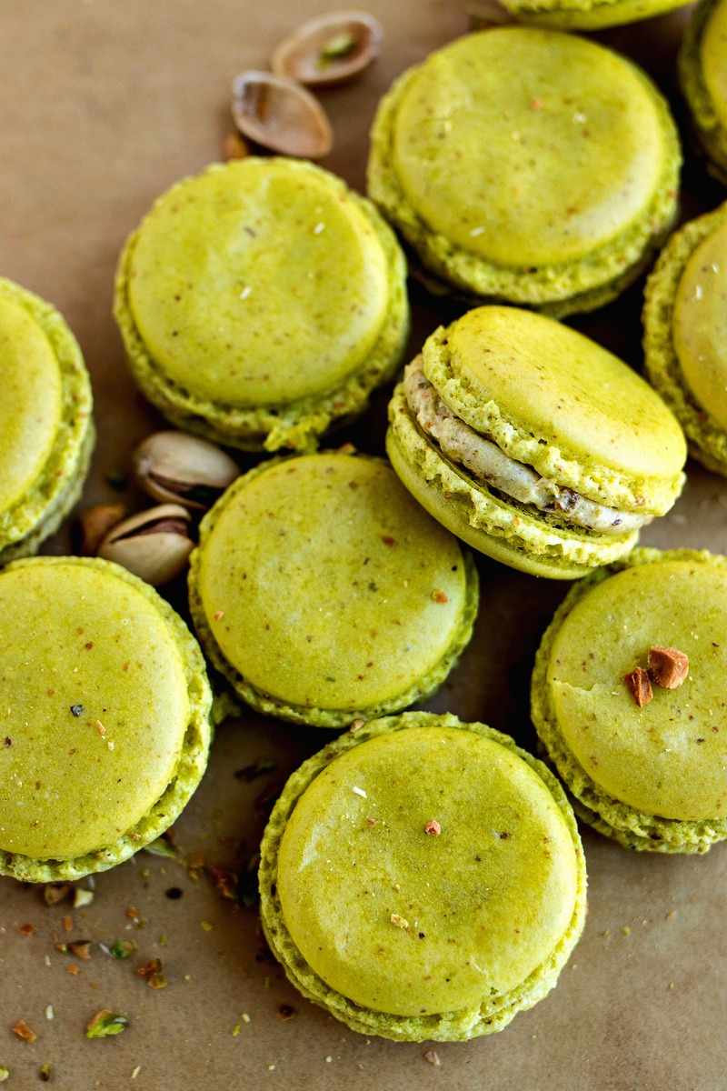 Pistachio Macarons with pistachios scattered around them