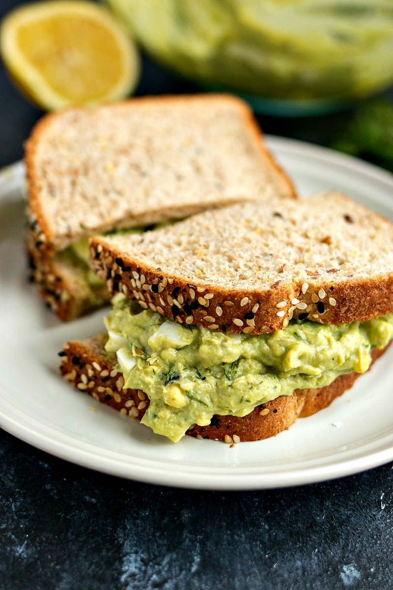 Avocado Egg Salad Sandwich on wheat bread cut in half